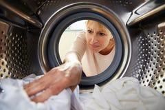 Woman Doing Laundry Reaching Inside Washing Machine Royalty Free Stock Photography