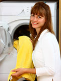 Woman doing laundry with smile. A smiling woman doing laundry in her home (house) holding yellow clothes stock photos