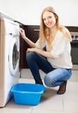 Woman doing laundry with washing machin Stock Image
