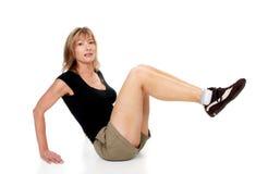 Woman doing leg raise. Isolated woman doing leg raise on a white background Stock Photo