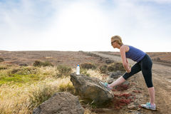 Woman Doing Leg Stretch Before Outdoor Jog. Woman stretching leg before an outdoor jog Royalty Free Stock Image