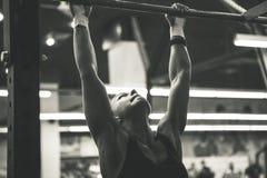Woman doing lifting up. On the gym bar stock photo