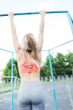 Woman doing lifting up on the gym bar. . Blonde fitness woman in sport wear with perfect fitness body on street workout. Performing abdominal exercises on the Royalty Free Stock Photography