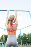 Woman doing lifting up on the gym bar. . Blonde fitness woman in sport wear with perfect fitness body on street workout. Performing abdominal exercises on the Stock Photography