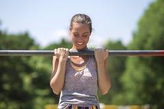 Woman doing lifting up on the gym bar at summer. Woman doing lifting up on the gym bar in the park at summet royalty free stock photos