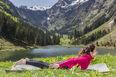 Woman doing Locust pose in yoga outdoors Royalty Free Stock Photos