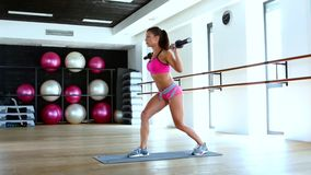 Woman and doing lunge with barbell and flexing muscles in gym stock video footage