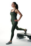 Woman doing a lunge on an exercise step. Image of a fit female doing a lunge Stock Photo
