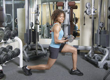 Woman doing lunges and curls. Woman working out doing lunges and curls with weights in a gym Royalty Free Stock Photo