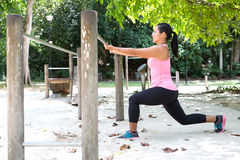 Woman doing lunges exercise in outdoor park. Sporty woman doing lunges exercise in outdoor park royalty free stock image