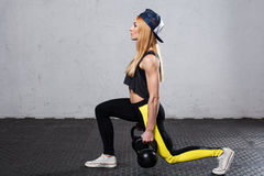 Woman doing lunges with kettlebells stock photography