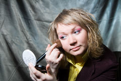 Woman doing make-up Stock Photography