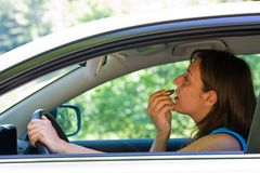 Woman doing make-up in car. Woman doing make-up while driving Royalty Free Stock Image