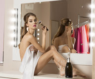 Woman doing make-up in changing room Royalty Free Stock Photo