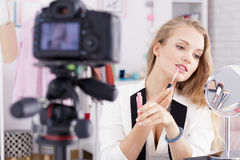 Woman doing make up. In front of camera royalty free stock photography