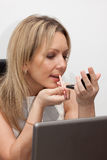 Woman doing make-up at work. The picture of 30 years old blonde young woman Royalty Free Stock Photos
