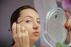 Woman is doing makeup Royalty Free Stock Photos