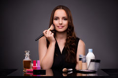 The woman doing makeup on dark background Stock Photo