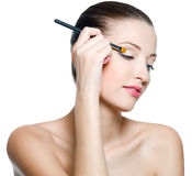 Woman doing makeup on eyes Stock Images