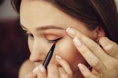 Woman doing makeup and painting black arrows. Stock Image
