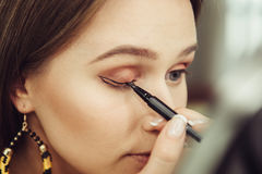 Woman doing makeup and painting black arrows. Stock Images