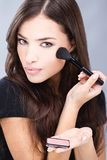 Woman doing makeup with powder brush Royalty Free Stock Photo