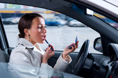 Woman is doing makeup on the run in car Stock Photo