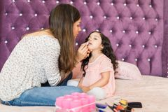 Woman Doing Makeup To Little Daughter With Lipstick royalty free stock photos