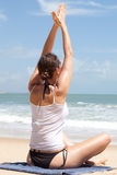Woman doing meditation in front of ocean Stock Image