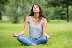 Woman Doing Meditation In Park. Young Woman Sitting On Green Grass Doing Meditation In Park Royalty Free Stock Photos