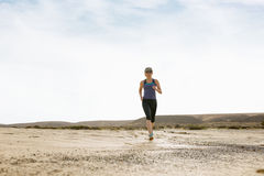 Woman Doing Morning Jog in the Desert. Woman in sunglasses and sportswear doing morning jog in the desert Stock Photos