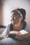 Woman doing mud facial masking at home spa stock photos