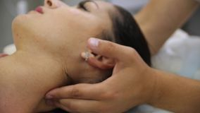 Woman doing neck massage at the reception of the chiropractor. Men`s hands do massage of the cervical spine to an stock footage