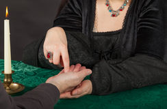 A woman is doing a palm reading. A dark dressed women is doing a palm reading stock image