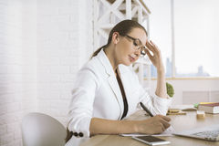 Woman doing paperwork side. Side view of thoughtful businesswoman doing paperwork in modern office. White brick wall background Royalty Free Stock Photography