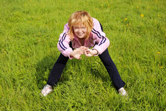 Woman doing physical exercises. Blond caucasian woman doing physical exercise in a meadow Stock Images