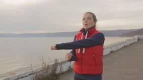 The woman is doing physical exercises on the lake coastline turning, rotating arms and stretching the muscles. stock video