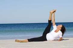 Woman doing pilates at the beach Stock Images