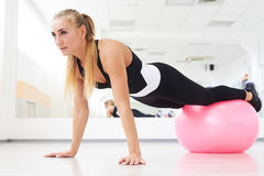 Woman doing pilates exercises with pink fitball in gym. Close-up shot of woman doing pilates exercises with pink fitball in gym Royalty Free Stock Images