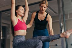 Woman doing pilates workout at the gym. Woman doing pilates workout with raised hands at the gym. Trainer guiding a pilates women at gym for correct posture stock photos