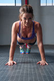 Woman doing plank exercise. Inside a gym royalty free stock photography