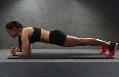 Woman doing plank exercise on mat in gym Stock Image