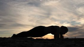 Woman doing plank hip twists on beach at sunset stock footage