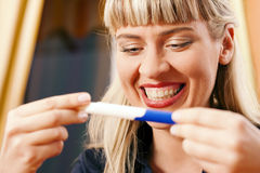 Woman doing pregnancy test being happy Royalty Free Stock Photos