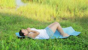 Woman doing press exercises on the lake in the morning. Overall plan stock video