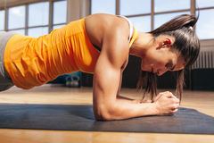 Woman doing press-ups in gym. Side view of attractive young woman doing core exercise on fitness mat in the gym. Female doing press-ups in health club Royalty Free Stock Photography