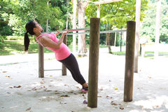 Woman doing pull up on exercise bar in a park. Beautiful woman doing pull up on exercise bar in a park royalty free stock photo