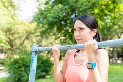 Woman doing Pull up at park. Asian young beautiful woman portrait stock photography