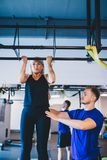 Woman doing pull-ups and a man securing her. Stock Photography