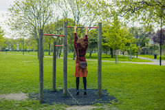 Woman doing pull ups in a park Stock Image